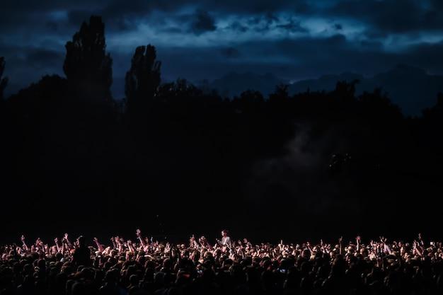 ステージからのスポットライトに照らされた夜のコンサートで観客の群衆