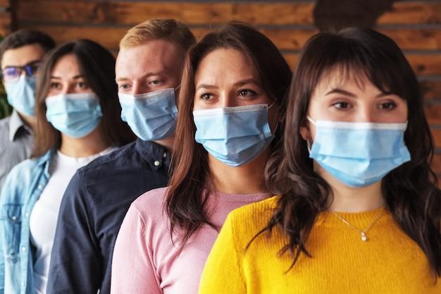 Толпа молодых людей в масках на лицах во время пандемии коронавируса