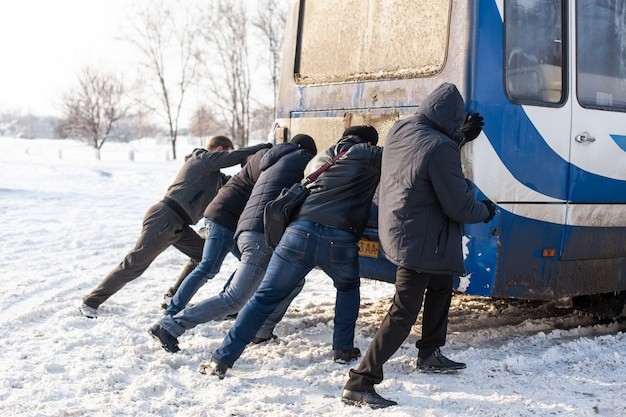 A crowd of people are pushing a bus that is stuck in the snow. severe weather conditions. snow paralyzes traffic