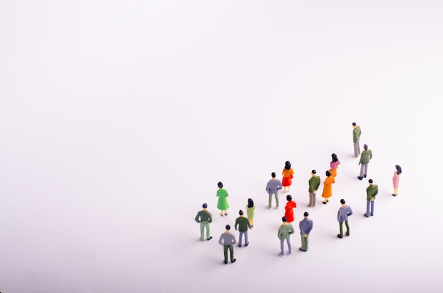 A crowd of people is standing and looking at the white background.
