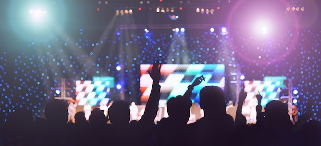 Crowd people in party enjoy dancing and show hands up in concert