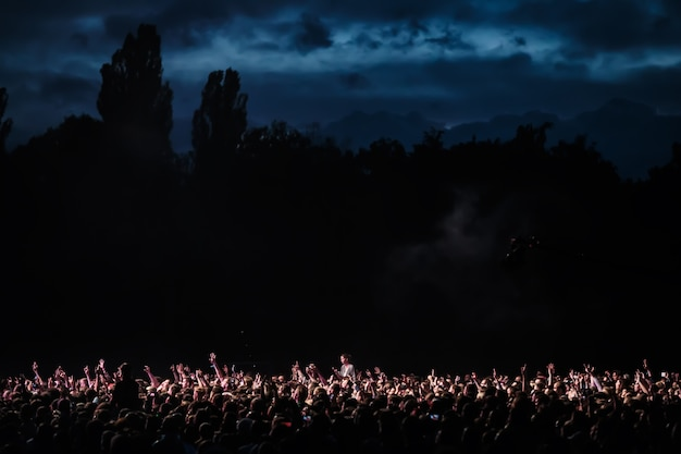 Crowd of spectators at a concert at night lit by a spotlight from the stage