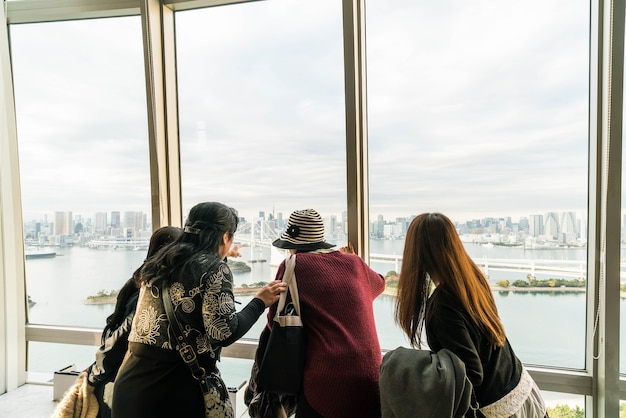 A crowd of tourists and locals enjoy the view of the tokyo bay from odaiba on a cloudy autumn afternoon.