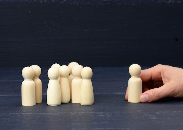 A crowd of wooden figures, opposite the hand is holding one figure