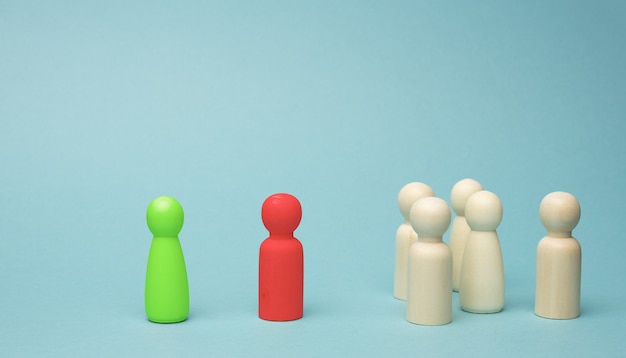 A crowd of wooden figurines, a negotiator and a free-standing green figurine. the concept of solving the problem between the team and the director, disputes, conflict of interest, dislike of the team
