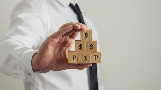 Crowdfunding investment concept - business investor holding wooden blocks with a dollar and p2p signs on them.