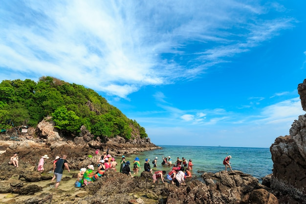 Crowds of sunbathing visitors enjoy a day trip boat ride to kai island, one of the most beautiful beaches and near the phi phi island of  thailand.