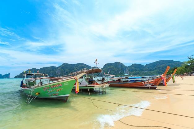 Crowds of sunbathing visitors enjoy a day trip boat ride to kai island