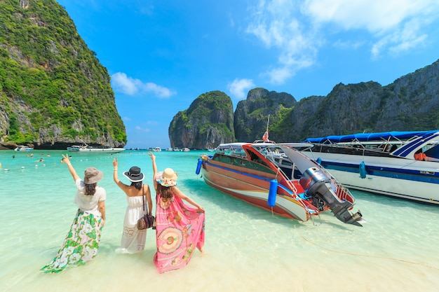 Crowds of sunbathing visitors enjoy a day trip boat ride to maya bay
