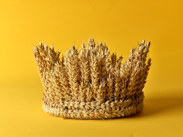 Crown made of wheat ears of cereals on a yellow background