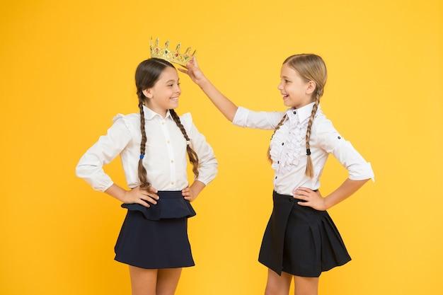 크라운은 그녀에게 적합합니다. 사랑스러운 작은 아이가 왕관을 쓴 귀여운 챔피언 소녀에게 상을 줍니다. 행복한 작은 승자와 챔피언 대관식. 챔피언이 선정되었습니다. 학교 대회 개념입니다. 왕실의 우정.