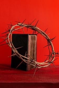 いばらの冠と古い聖書または赤い背景の本、コピースペース。