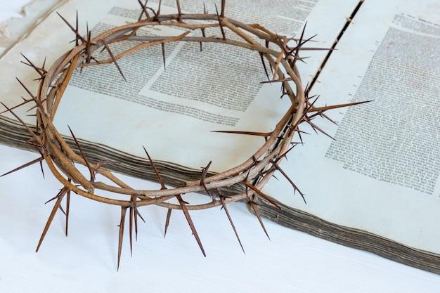 いばらの冠と白い背景の古い聖書や本、コピースペース。