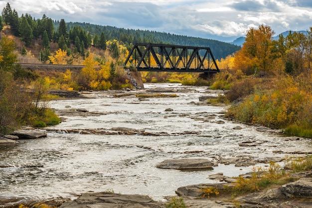 Река кроуснест в осенний сезон листвы, на заднем плане железный мост для железнодорожных путей. альберта, канада.