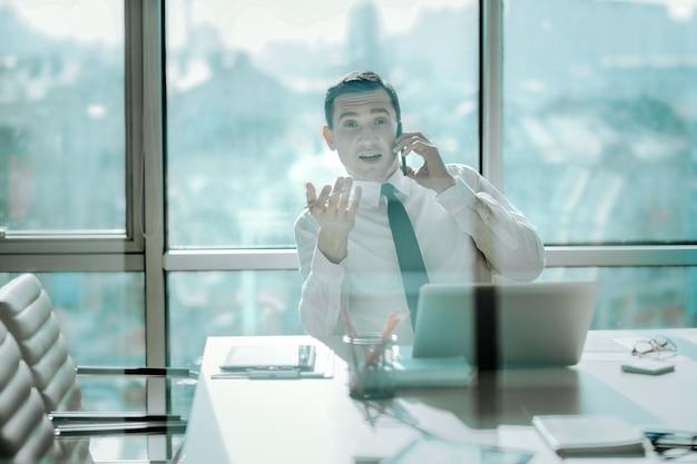重要な議論。大きな窓のある彼のオフィスのテーブルに座って、電話で感情的に交渉する魅力的な若い男