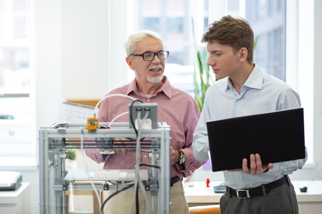 重要なレッスン。ラップトップを持っている男性が3dプリンターの構成を変更する方法をインターンに教える明るいシニアエンジニア