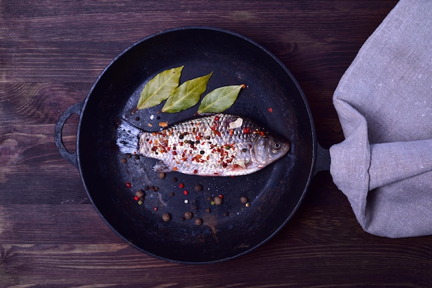 Crucian carp in spices on a black cast-iron frying pan