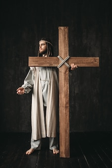 Crucifixion of jesus christ, symbol of christian religion. man with cross on black