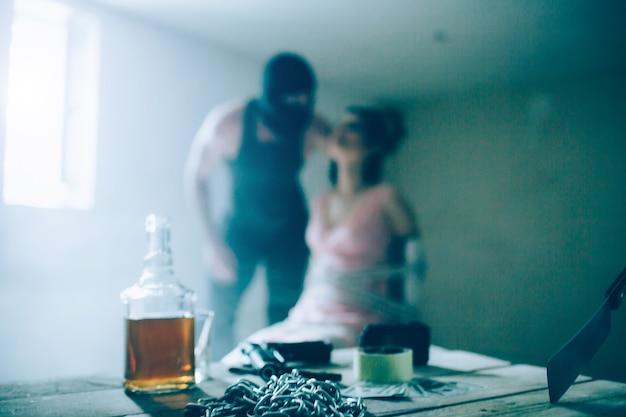 Жестокий и злой мужчина в маске стоит рядом со своей жертвой и держит ее за волосы. девушка смотрит вверх. она привязана к стулу. на столе бутылка алкоголя, цепочки, скотч и нож.