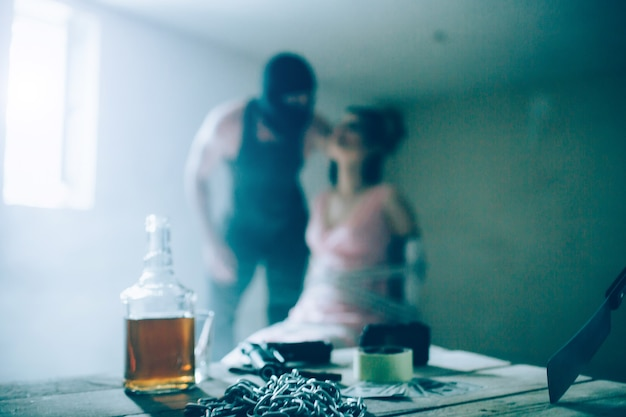 Cruel and angry man in mask is standing besides his victim and holding her hair. girl is looking up. she is tied to chair. there are bottle of alcohol, chains, scotch and knife on the table