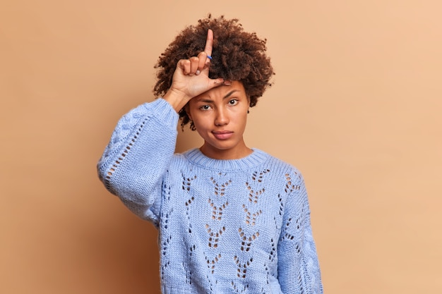 La donna seria e maleducata crudele fa perdere il gesto tiene il dito alzato sulla fronte insulti qualcuno prende in giro le persone che indossano un maglione blu isolato sul muro beige