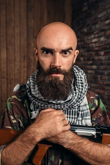 Cruel terrorist in uniform with kalashnikov rifle, male mujahadeen with weapon. terrorism and terror, soldier in khaki camouflage