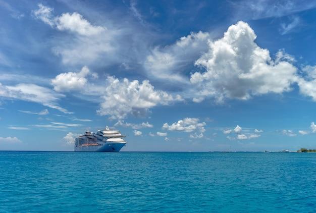 Круизный лайнер в кристально голубой воде и красивых облаках