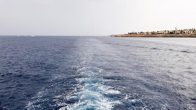 Круизный лайнер или тропа на поверхности синего красного моря. след корабля морской воды с белой пенистой волной. вид сверху на глубокий океан. перспектива волны белой воды.