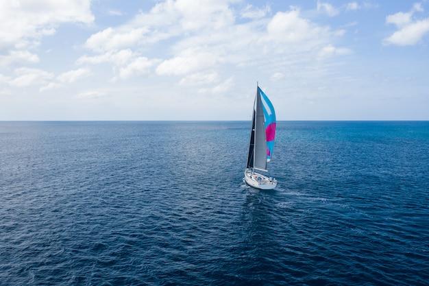 Круизный отдых. аэрофотосъемка яхты с розовым парусом на морской воде