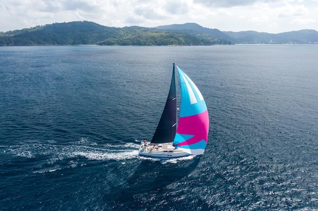 クルーズ休暇。海の水にピンクの帆とヨットの航空写真