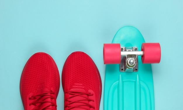 Доска круизера и красные кроссовки на синем фоне.