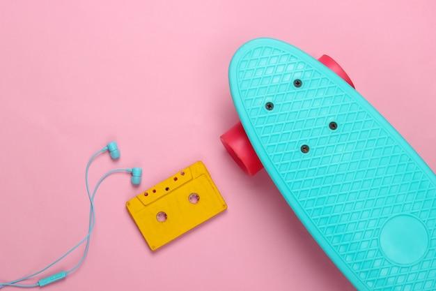 クルーザーボードとレトロなオーディオカセット、ピンクのパステルカラーのイヤホン