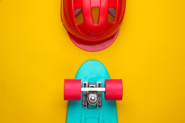 黄色の背景に巡洋艦ボードと安全ヘルメット。スポーツ用保護具。子供時代。上面図