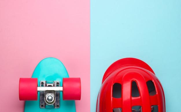 ピンクブルーのパステルカラーの背景にクルーザーボードと安全ヘルメット。スポーツ用保護具。子供時代。上面図