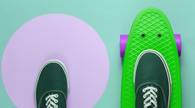 분홍색 파스텔 원이 있는 녹색 배경에 크루저 보드와 운동화. 청소년 힙스터 개념입니다. 여름 재미. 평면도