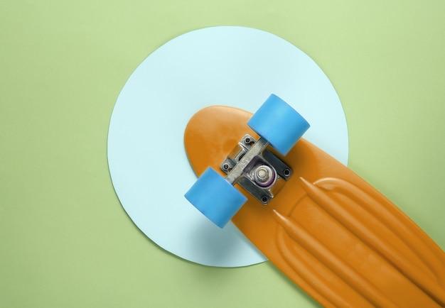 파란색 파스텔 원이 있는 녹색 배경 한가운데에 있는 크루저 보드. 청소년 힙스터 개념입니다. 여름 재미. 평면도
