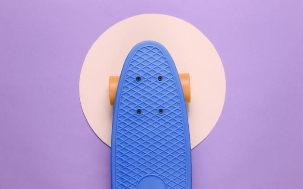 노란색 파스텔 원이 있는 보라색 배경 한가운데에 있는 크루저 보드. 청소년 힙스터 개념입니다. 여름 재미. 평면도