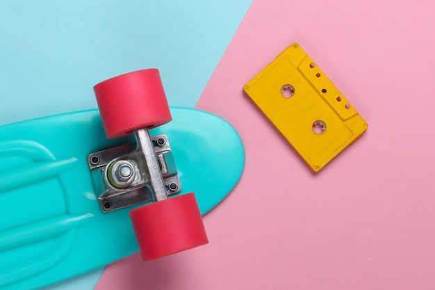 Cruiser board and retro audio cassette on a blue pink pastel