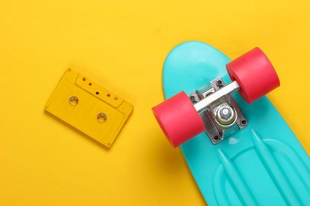 Cruiser board and retro audio cassette on yellow