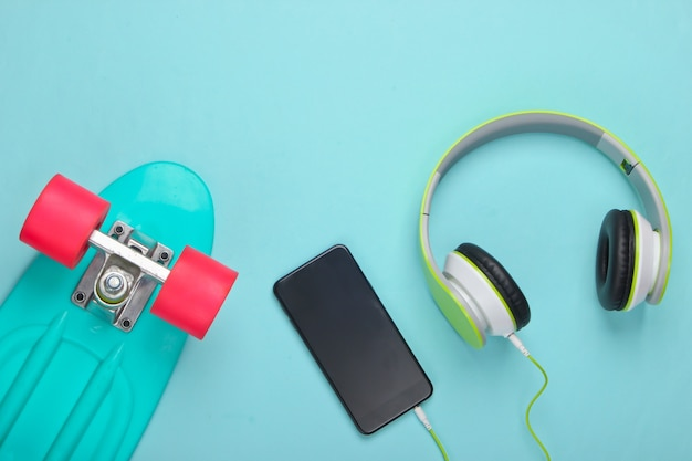Cruiser board and stereo headphones with smartphone on blue pastel surface