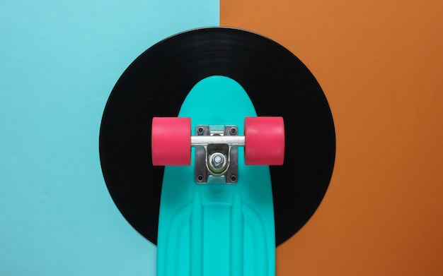 Cruiser board on vinyl record. brown blue background. youth retro style concept.