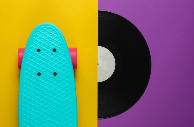 Cruiser board and vinyl records on purple yellow background. youth retro style concept.