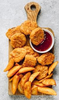 Жареные крошки с жареным картофелем и небольшой миской соуса.