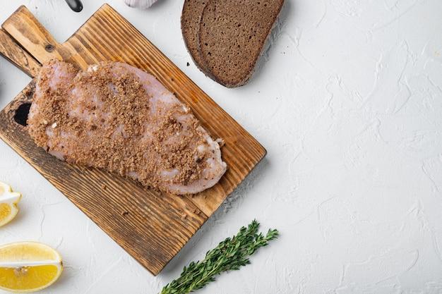요리하지 않은 닭 가슴살 재료를 흰색 배경에 깔고, 텍스트를 위한 공간이 있는 평평한 눕습니다.
