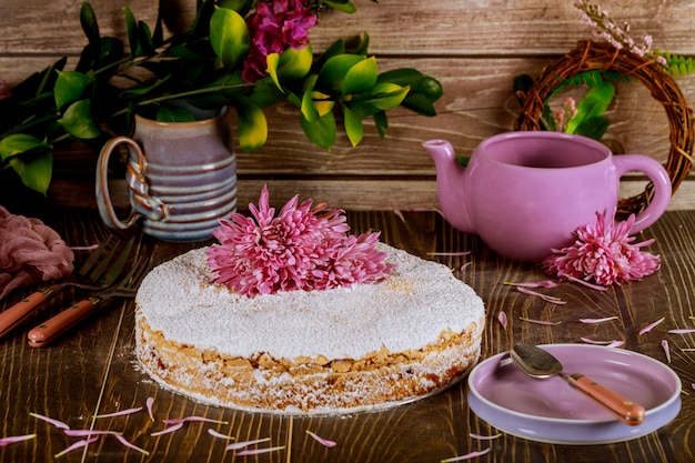 Crumble cake with fresh flowers, plate, teapot