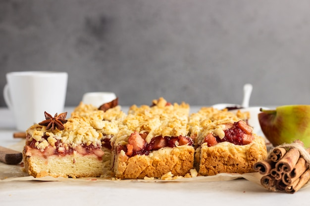 Crumble cakes with apple, red berry jam and spices filling