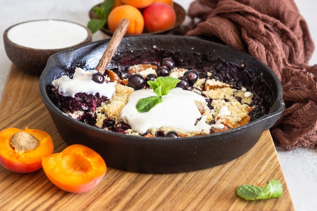 Crumble in cast iron pan with blackcurrant and apricot, natural yogurt and mint.