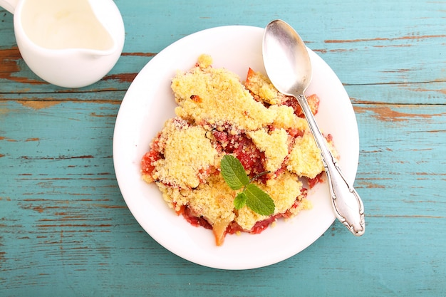 Crumble with strawberries in white plate on a blue background