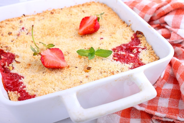 Crumble with strawberries in white plate on a white background