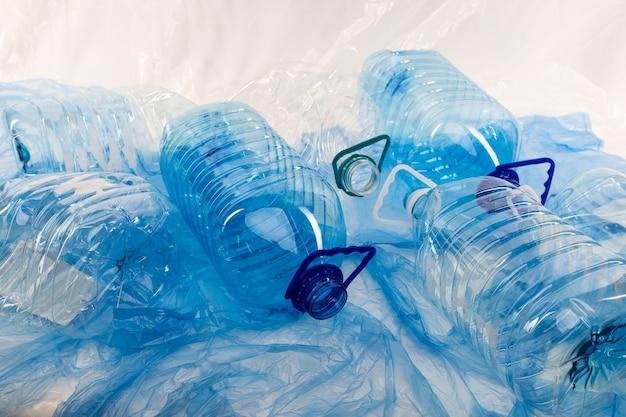 崩れた素材。プラスチック製の青い材料で覆われた表面に置かれた廃棄された透明な水筒